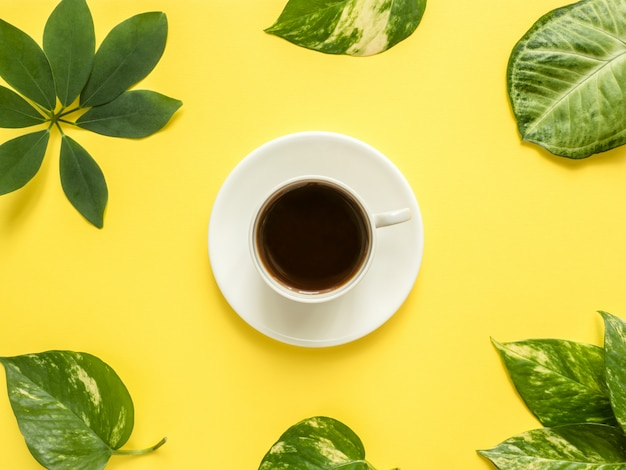 Tasse de café au centre sur fond jaune avec des feuilles vertes.