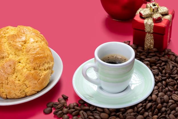 Une tasse de café au lait et des biscuits quelques grains de café avec décoration de nol sur un fond rose