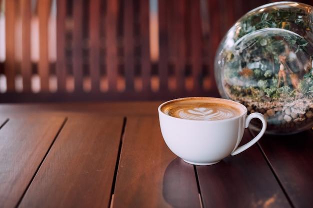Tasse de café au lait chaud sur table en bois avec sphère en verre