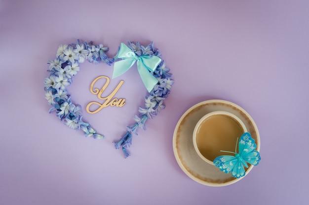 Tasse de café au lait et coeur faite de fleurs de jacinthe sur fond violet.