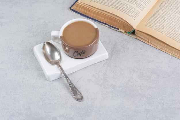 Tasse de café au lait, cuillère et livre sur la surface de la pierre. photo de haute qualité