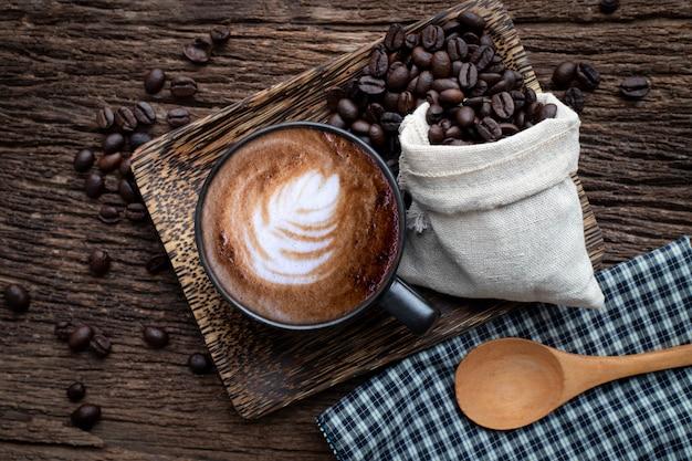 Tasse de café au lait avec des grains de café sur la table en bois.
