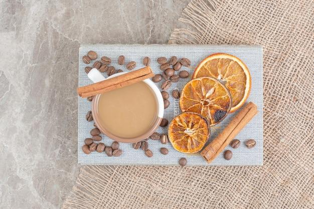 Tasse de café au lait avec grains de café et tranches d'orange sur le livre. photo de haute qualité