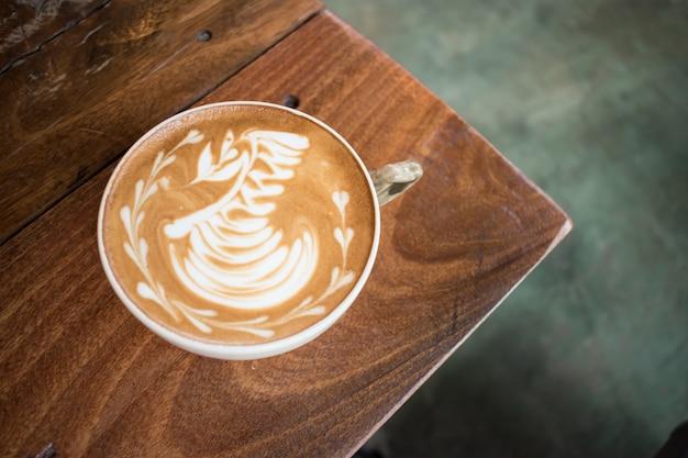 Une tasse de café au lait latte cygne dans le coin d'une table en bois.