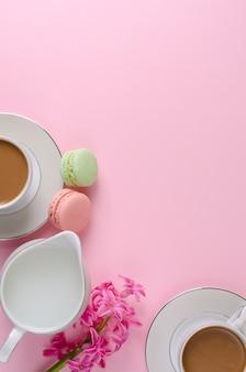Tasse de café au lait, macarons, pot de lait rose pastel