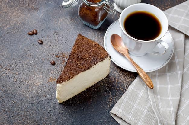 Tasse de café au lait avec un morceau de fromage à pâte molle dans le café moulu