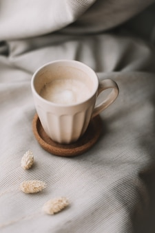 Tasse de café au lait sur plaid beige