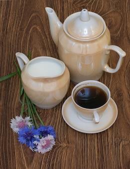 Tasse de café au lait, pot de café et bleuets sur table en bois