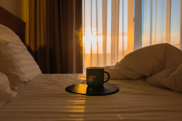 Tasse de café au lit à l'aube du lever du soleil avec une tasse de café au lit café chaud au lit au réveil