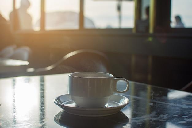 Tasse de café au matin avec la lumière du soleil. mise au point douce.