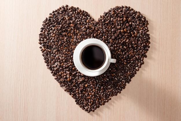 Tasse à café au milieu de la forme des grains de café d'amour sur la surface en bois