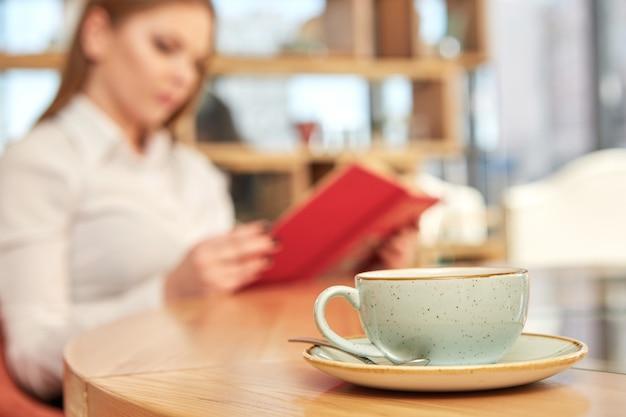 Tasse à café au premier plan, femme lisant un livre