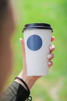 Tasse à café avec autocollant bleu dans la main des filles