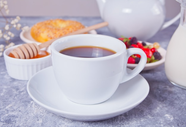 Tasse de café, baies, bagel et miel au petit déjeuner.