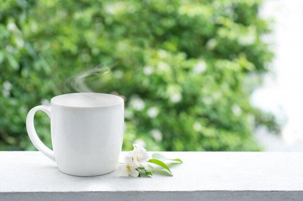 Tasse de café sur le balcon au matin avec des fleurs blanches