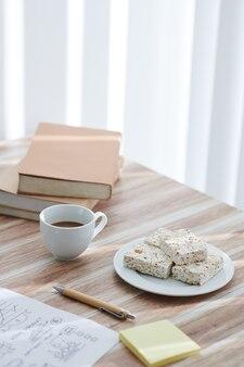 Tasse de café et barres de pop-corn sur le bureau à côté du document avec des graphiques et une pile de livres