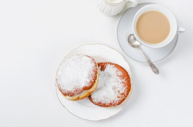 Tasse de café et un beignet avec de la confiture pour le petit déjeuner