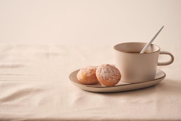 Tasse de café avec des beignets pour le petit déjeuner sur fond clair