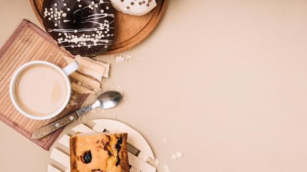 Tasse à café avec beignets et tarte sur table