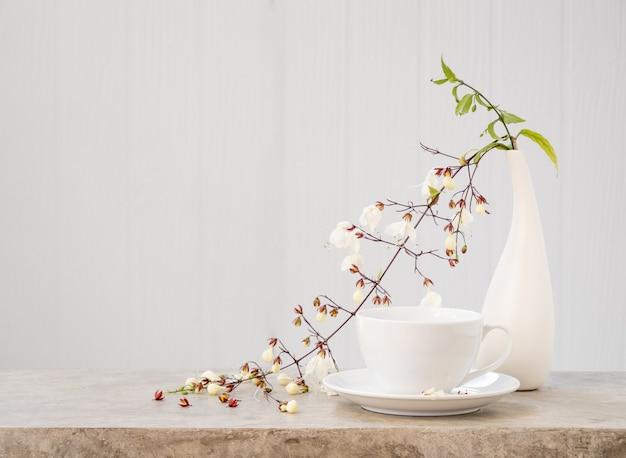 Tasse à café et belle fleur de clerodendron hochant la tête dans un vase moderne situé sur une table en béton avec fond de bois blanc