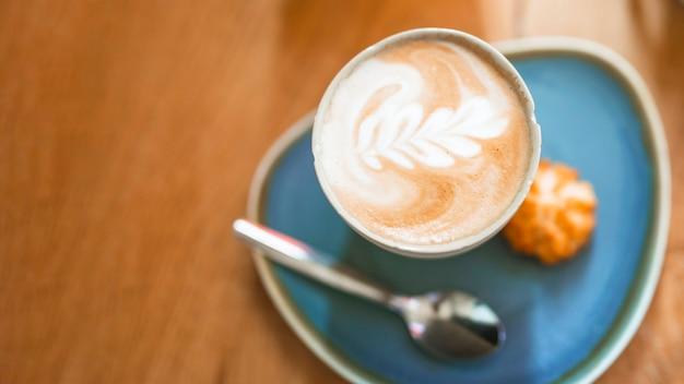 Tasse de café avec belle latte art sur table en bois