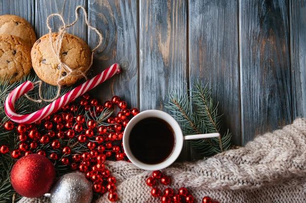 Tasse de café et biscuit aux pépites de chocolat entouré d'un décor festif de vacances d'hiver. esprit de noël et concept de loisirs. branche de sapin boule de ficelle rouge et mélange de canne en bonbon.