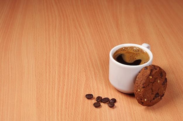 Tasse à café et biscuits au chocolat sur un fond en bois avec espace copie