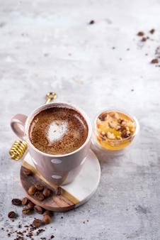 Tasse à café avec des biscuits au chocolat sur fond de pierre avec du miel et bâton de miel en métal