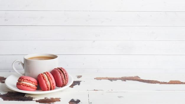 Tasse de café et biscuits au macaron sur une assiette sur un tableau blanc. espace de copie