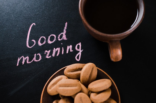 Tasse de café et de biscuits sur un fond sombre. bonjour inscription.