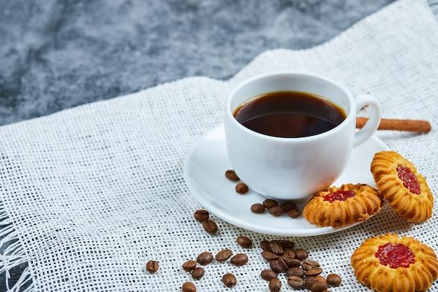 Une tasse de café, des biscuits, des grains de café et de la cannelle.
