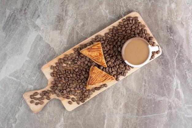 Tasse de café, biscuits et grains de café sur planche de bois. photo de haute qualité