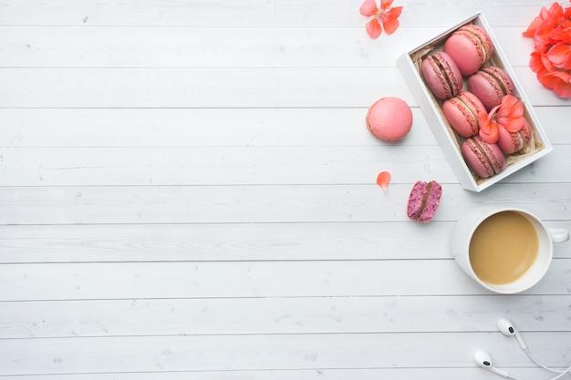 Tasse de café, biscuits macaron dans une boîte, fleurs sur fond blanc avec espace de copie