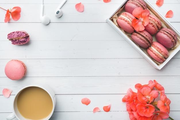Tasse de café, biscuits macaron dans une boîte, fleurs à plat poser