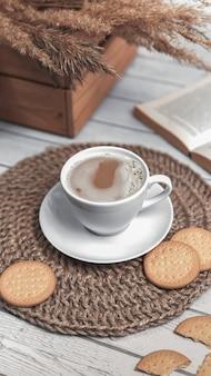 Tasse de café et biscuits sur napperon en jute en osier.