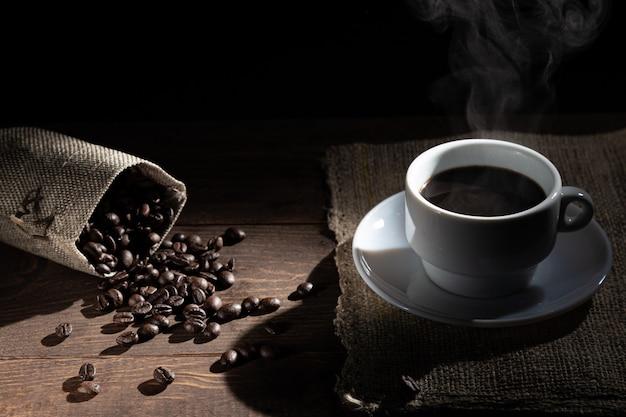 Tasse de café blanc et grains de café renversés du sac