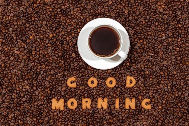 Tasse de café blanc et mots bon matin en lettres de biscuit sur fond de grain de café foncé