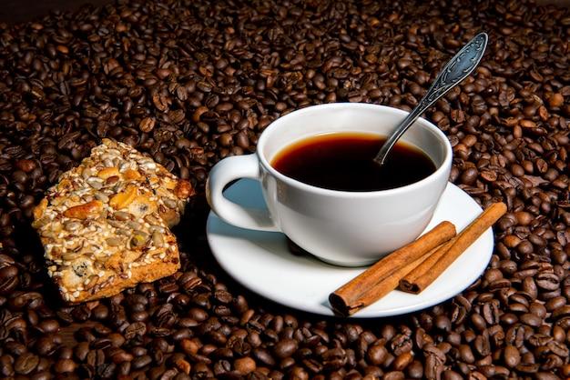 Tasse à café blanche, bâtons de cannelle et biscuits sur le fond des grains de café