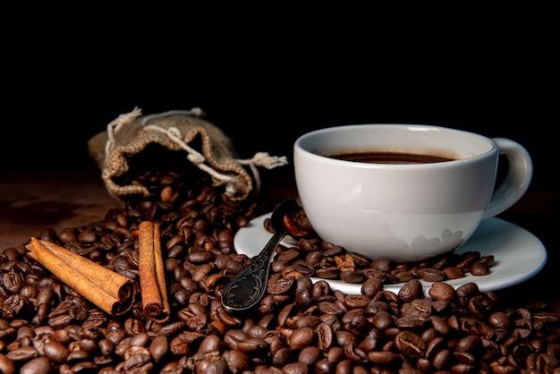 Tasse à café blanche, bâtons de cannelle et grains de café