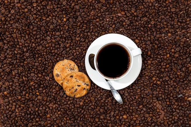 Tasse à café blanche et biscuits sur le fond de grains de café, vue de dessus