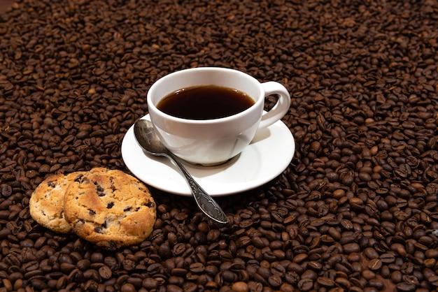 Tasse à café blanche et biscuits sur le fond des grains de café