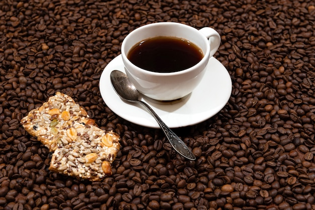 Tasse à café blanche et biscuits sur les grains de café