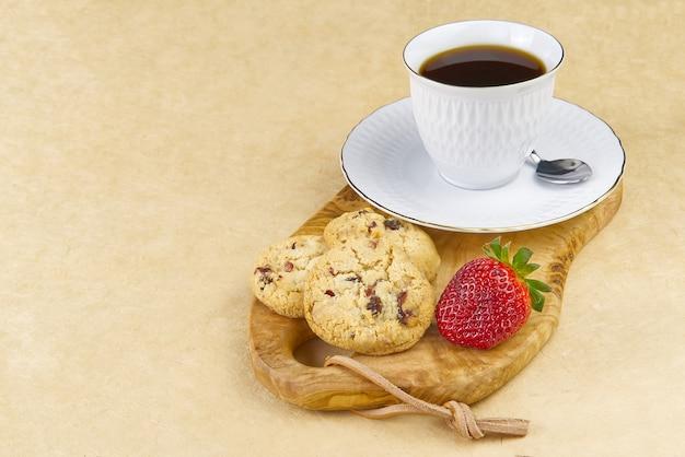 Tasse à café blanche avec une bordure dorée sur une planche en bois d'olivier.