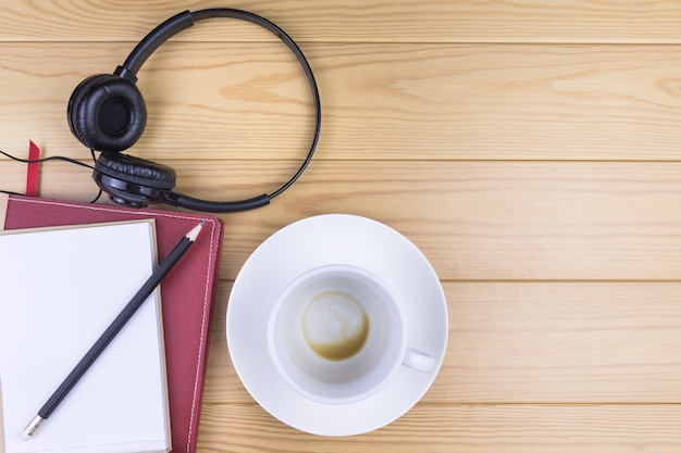 Tasse à café blanche, cahier, crayon et casque sur table en bois