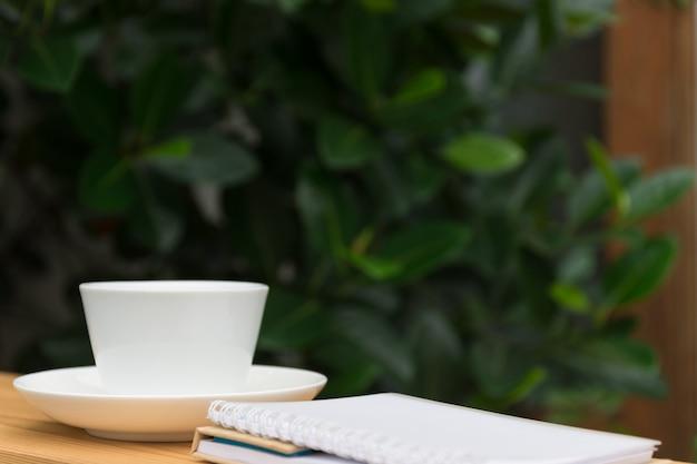 Tasse à café blanche et cahier sur un jardin en bois en arrière-plan.