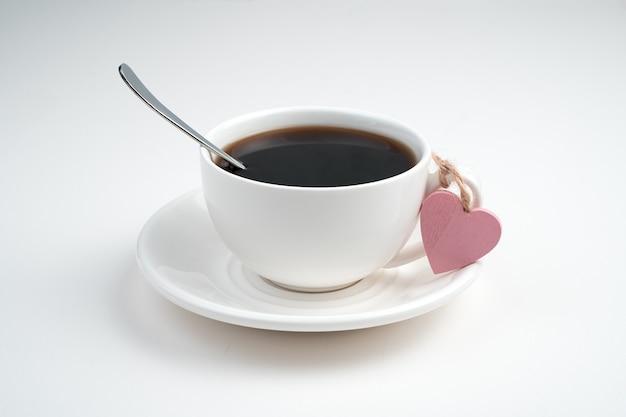 Une tasse à café blanche et un cœur rose attaché à la poignée de la tasse