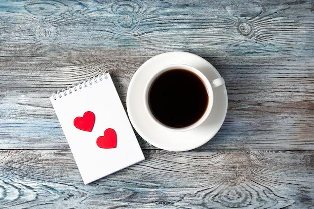 Tasse à café blanche et deux coeurs rouges sur un bloc-notes sur un fond en bois.