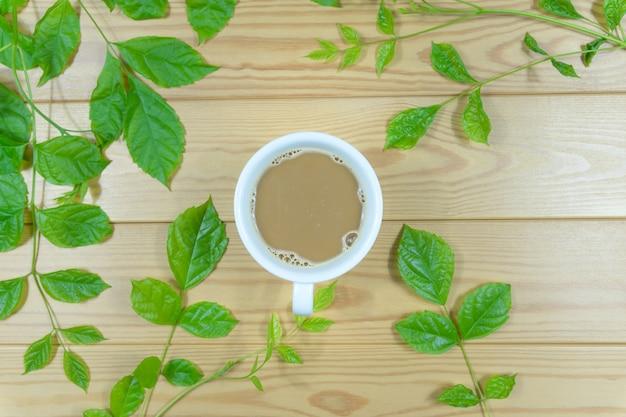 Tasse à café blanche entourée de feuilles vertes sur une table en bois.