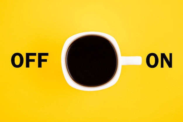 Tasse de café blanche est allumée. concept sur fond jaune.