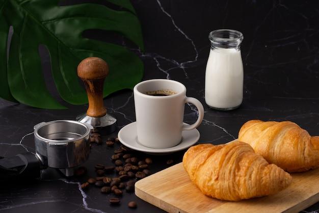 Une tasse de café blanche a été placée à côté d'une bouteille de lait et un croissant sur une planche à découper, des grains de café et des moulins sur un sol en marbre.